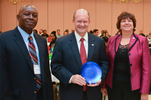 U.S. Sen. Chris Coons (center) receives the Friends of Extension Award from Albert Essel of Delaware State University and Michelle Rodgers of UD.