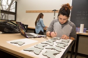 Students prepare for the philadelphia flower show installation, 2015. Sydney Bruck paints laser cut wood plant labels.